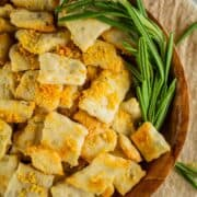 wooden bowl filled with homemade crackers topped with parmesan cheese and fresh rosemary sprig