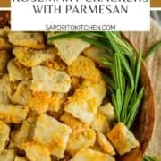 square homemade crackers topped with parmesan cheese in a wooden bowl with a sprig of rosemary