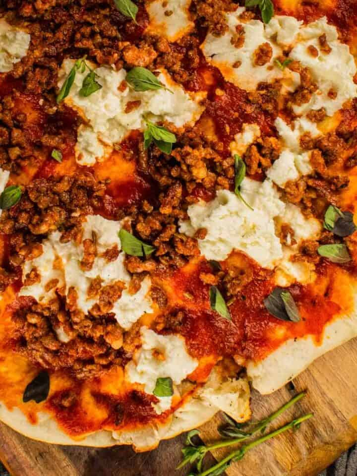 grilled pizza on a wooden cutting board topped with marinara, ricotta, sausage and fresh oregano leaves