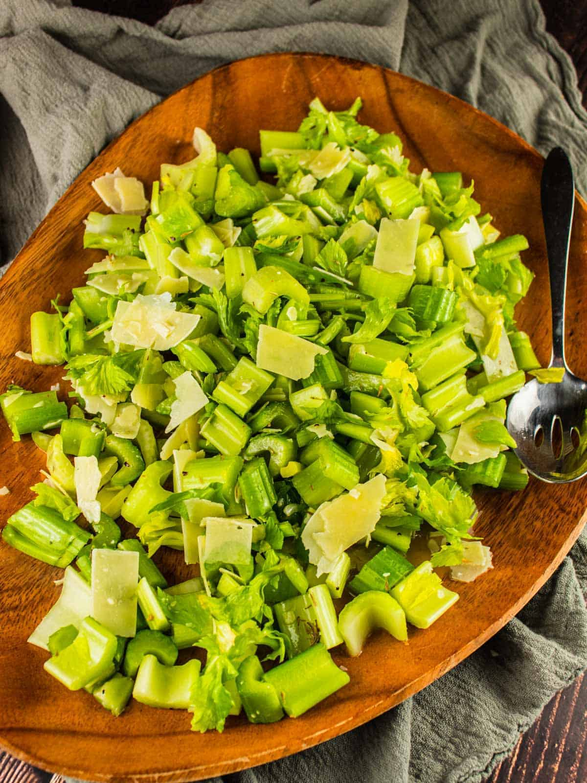 celery and parmesan salad on a wooden tray with a metal spoon