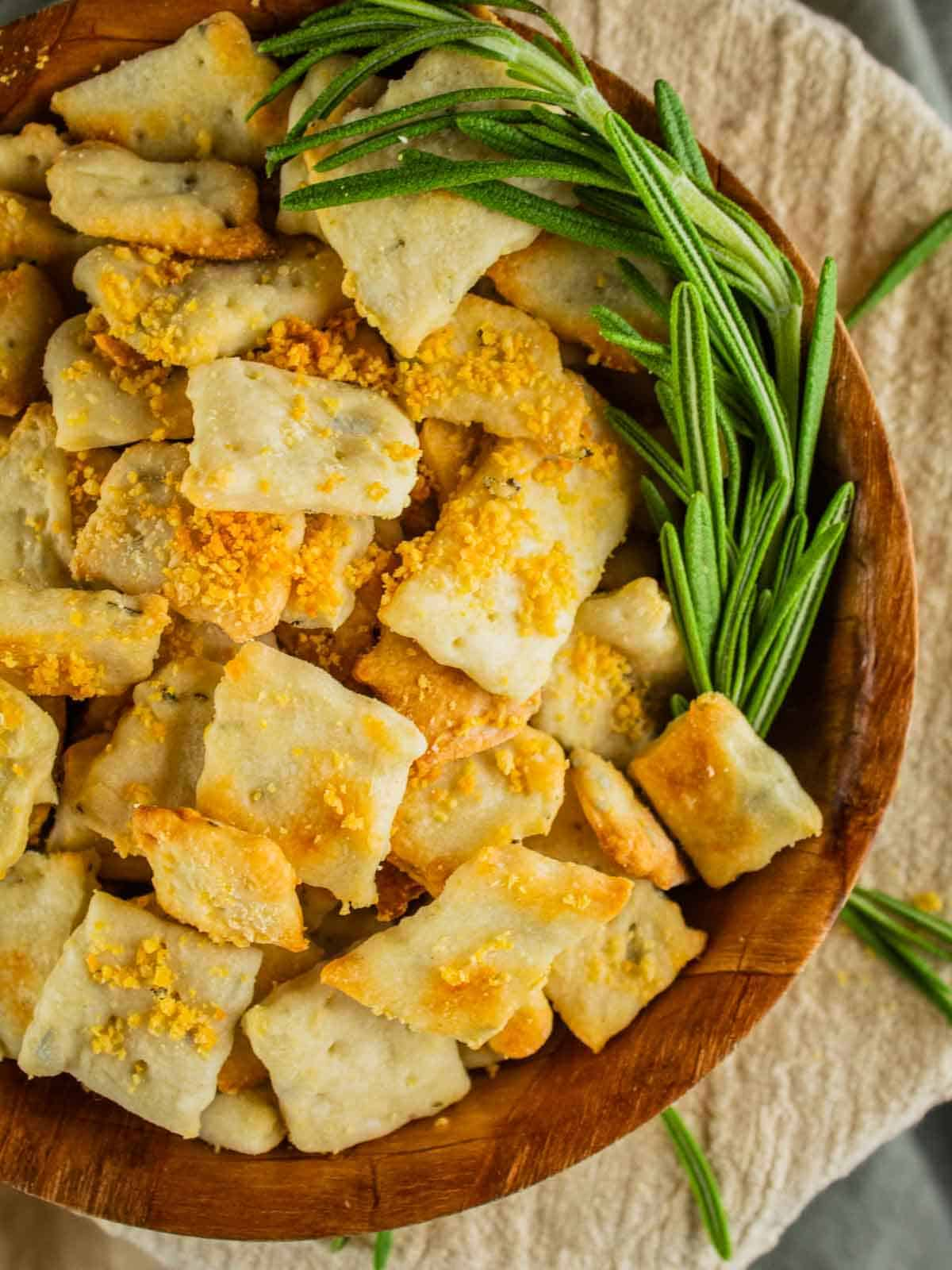 wooden bowl filled with homemade crackers topped with parmesan cheese and fresh rosemary next to it