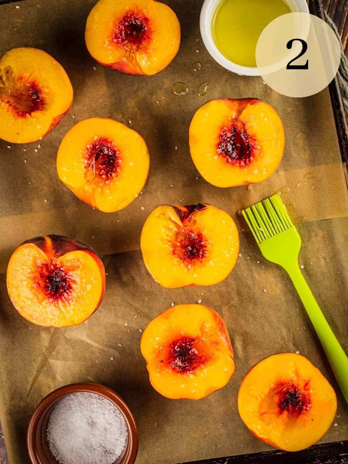 peach halves brushed with olive oil and sprinkled with salt on a sheet pan
