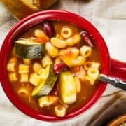 minestrone soup in a red ceramic soup crock with a spoon
