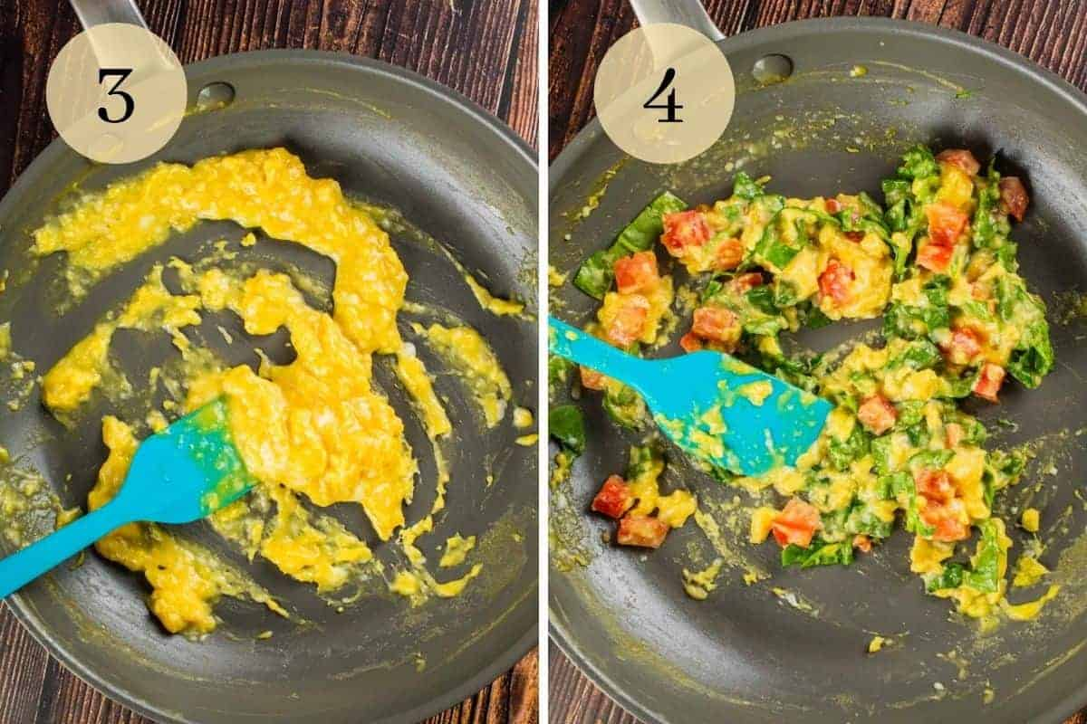 scrambled eggs cooking in a pan and a rubber spatula stirring in  spinach and tomatoes