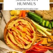 hummus in a wooden bowl drizzled with sriracha and next to crackers and vegetables