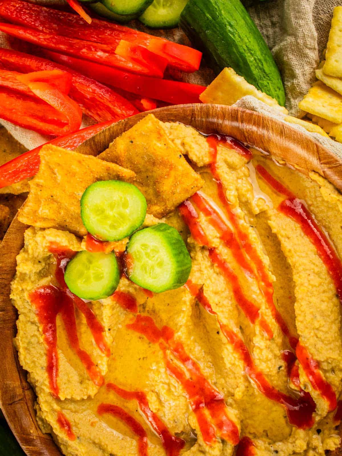hummus drizzled with sriracha in a wooden bowl with sliced cucumbers and crackers dipped in it