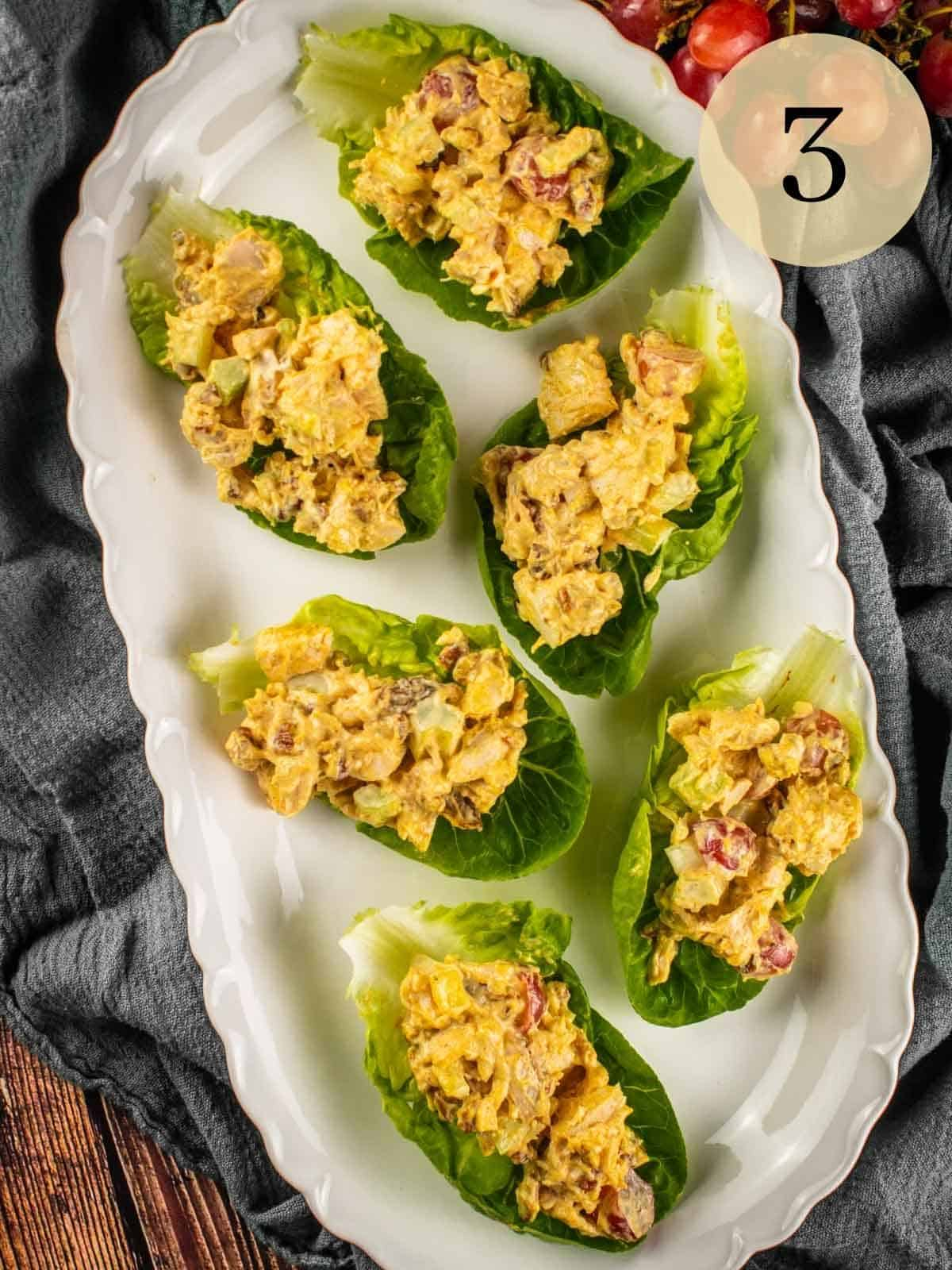 curry chicken salad on lettuce cups on a white oval platter