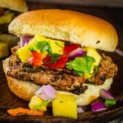 grilled turkey burgers on a bun topped with fresh pineapple salsa