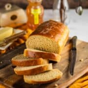 sliced honey wheat bread loaf on a cutting board with a knife and yellow napkin under it