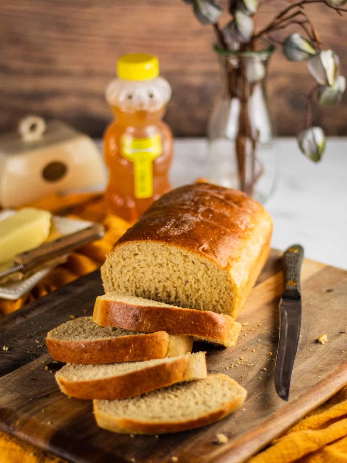 loaf of bread sliced on a wooden cutting board with knife, butter and honey