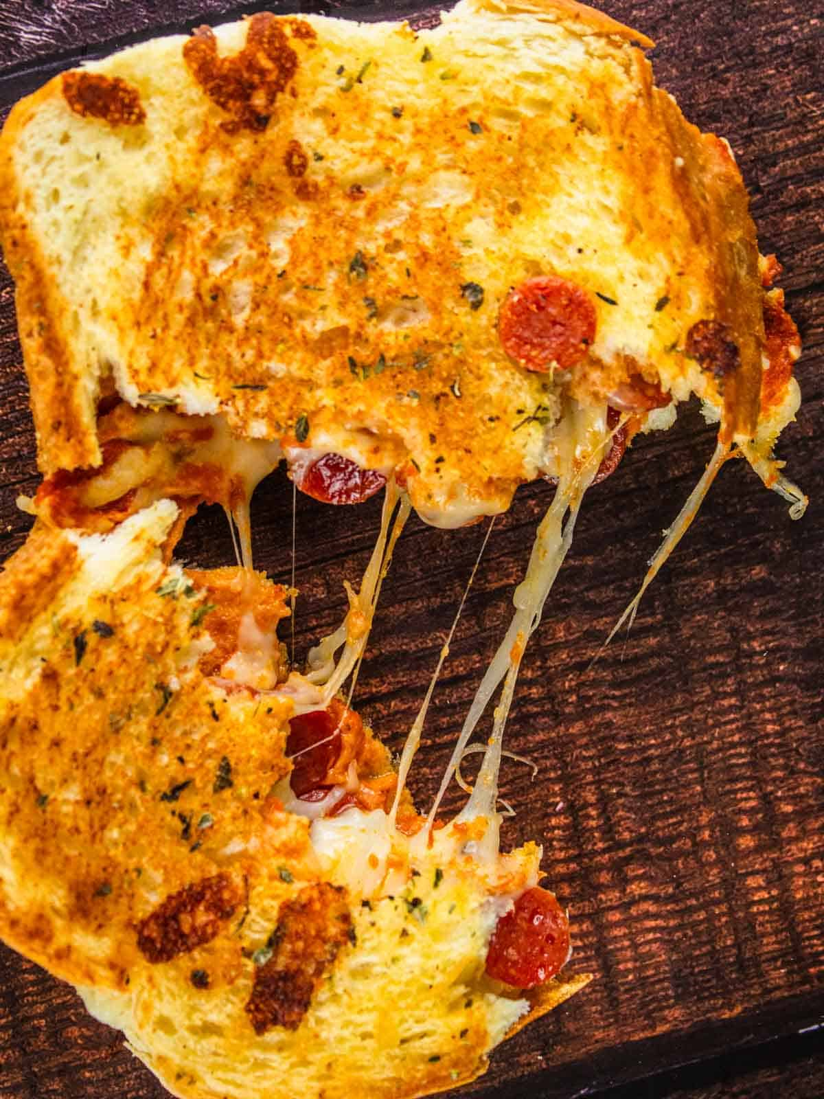 pizza grilled cheese pulled apart in a the middle with cheese stringing from it