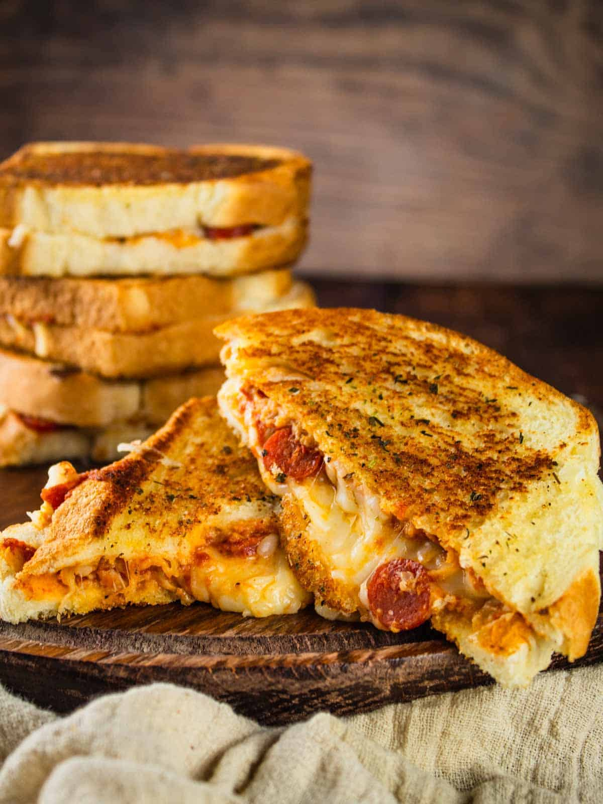 two halves of a pizza grilled cheese with pepperoni stacked on each other with a stack of grilled cheese in the background