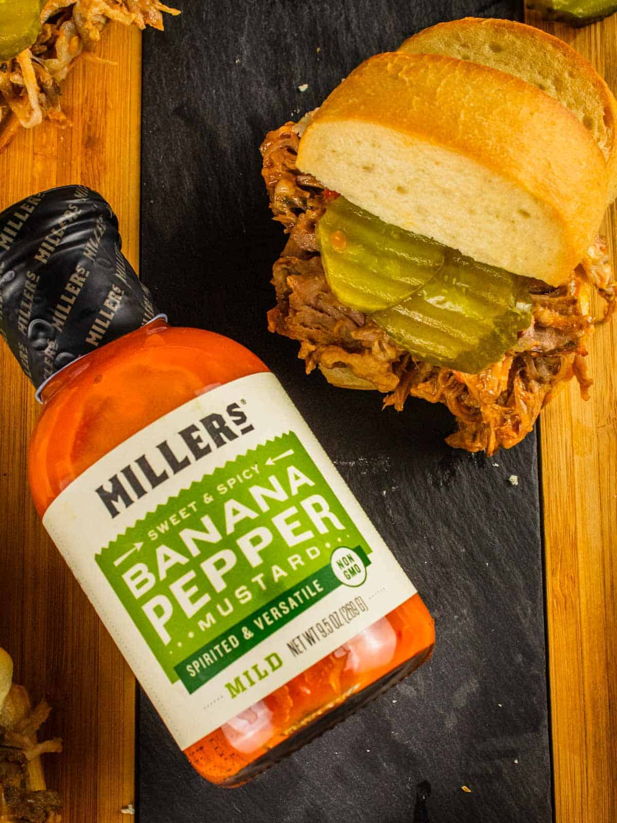 bottle of millers banana pepper mustard next to a pulled pork slider with pickles
