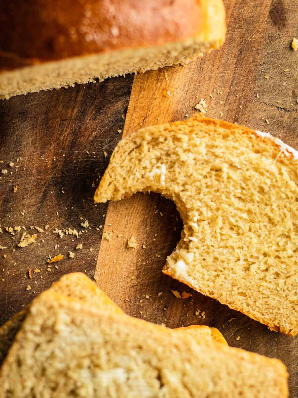 slice of homemade bread on a wooden cutting board with a bite taken from it