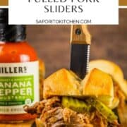pulled pork slider with pickles with a knife sticking in it