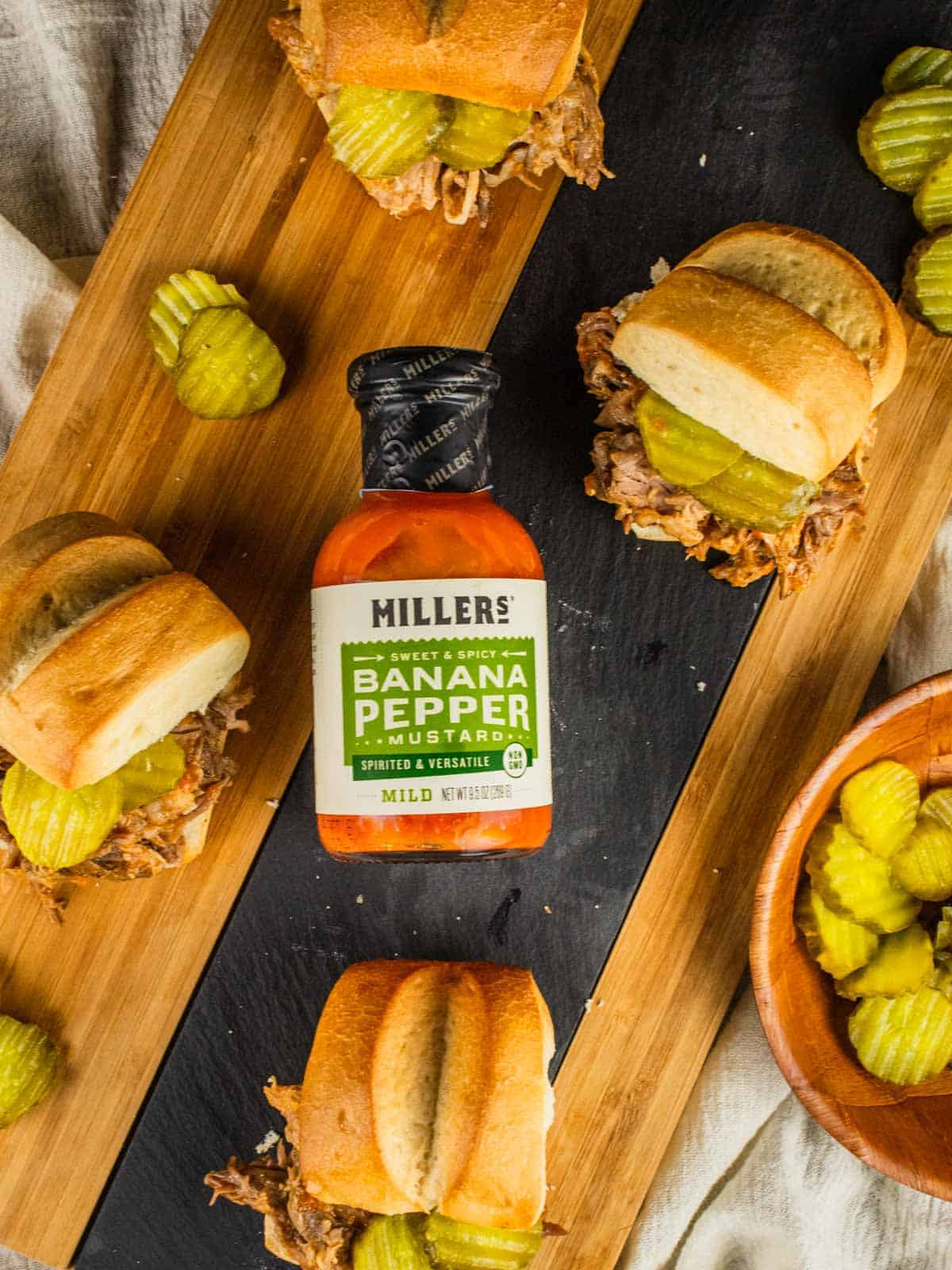pulled pork on slider buns with pickles around a bottle of millers mustard on a cutting board