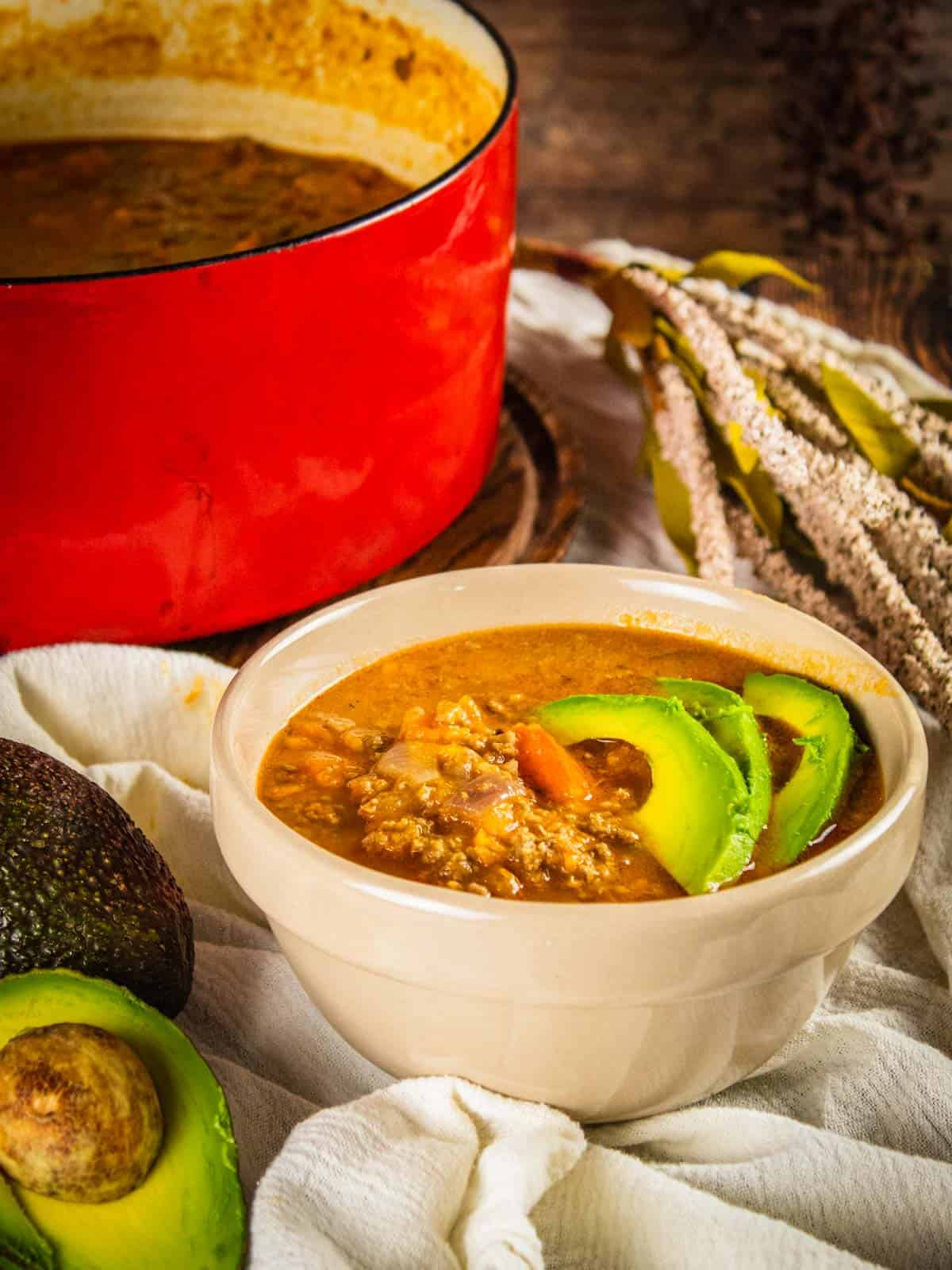 bowl of sweet potato turkey chili topped with sliced avocado with avocados next to it and a red pot in the background