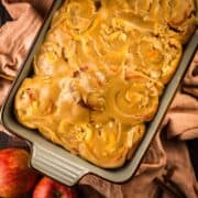 baking dish with apple cinnamon rolls topped with caramel frosting next to fresh apples