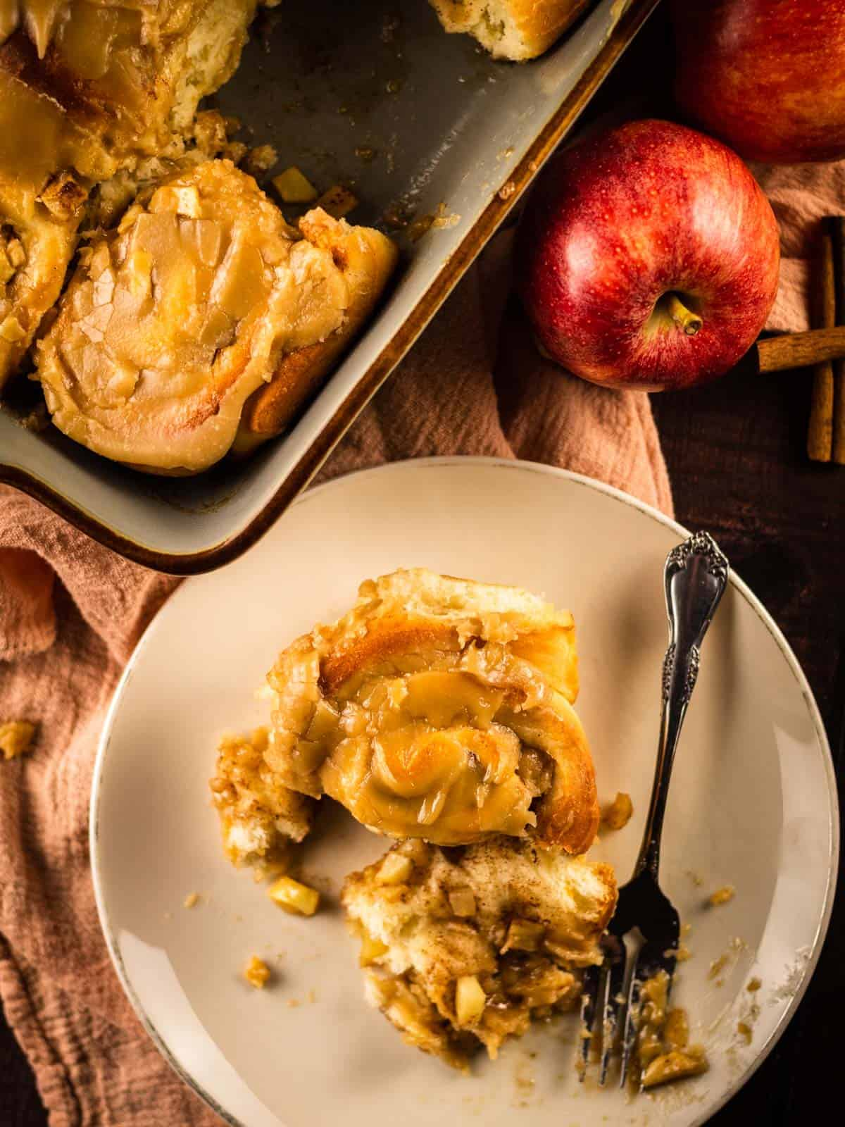 apple cinnamon roll on a plate and in a pan with fresh apples next to it