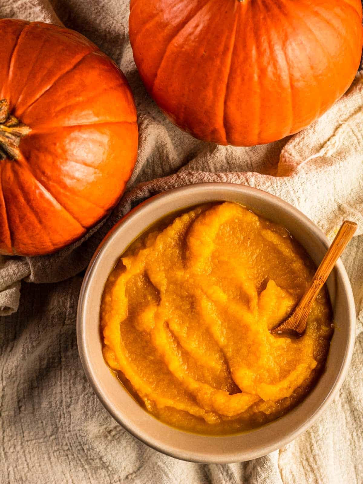 two pumpkins next to a tan ceramic bowl of pumpkin puree with a small wooden spoon