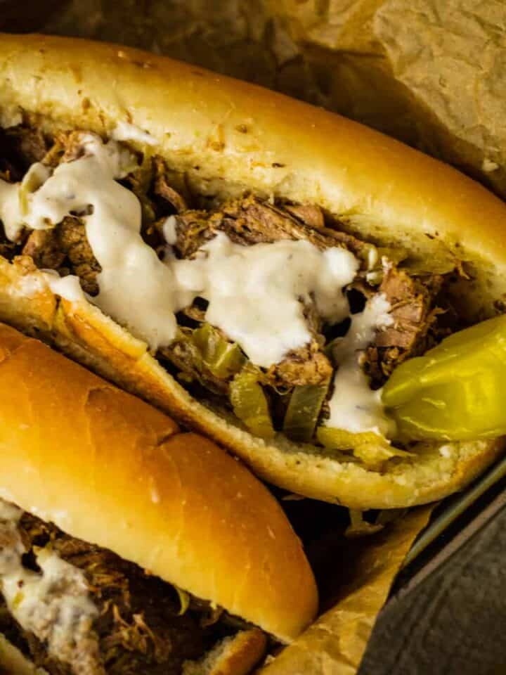 shredded beef with a whole pepperoncini on a hoagie roll with horseradish sauce