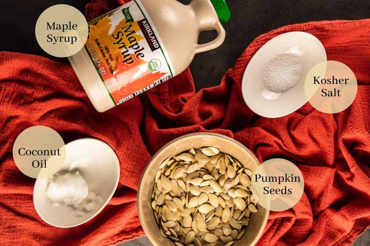 maple syrup bottle, bowl of kosher salt and coconut oil and bowl of raw pumpkin seeds