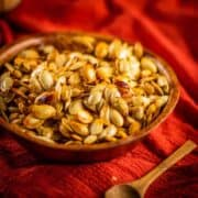 roasted pumpkin seeds in a wooden bowl next to a small wooden spoon