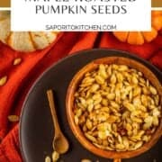 wooden bowl of roasted pumpkin seeds on a brown plate with pumpkins next to it