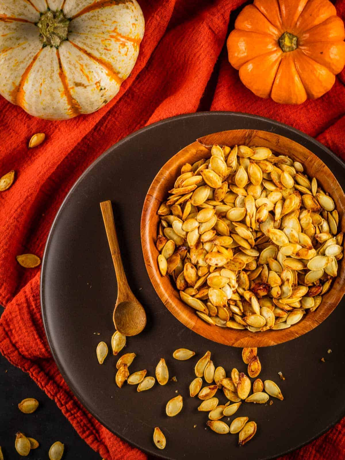 pumpkin seeds in a wooden bowl on a brown plate with a wooden spoon and pumpkins