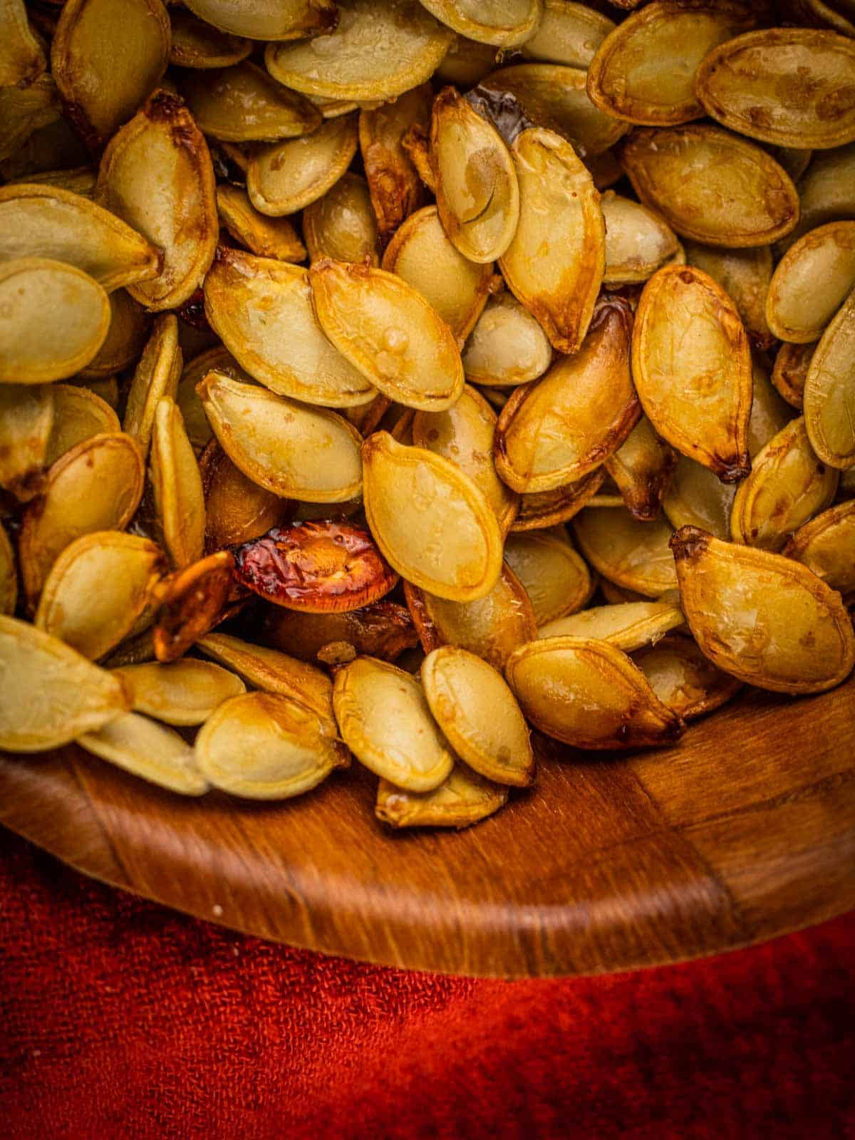 close up shot of roasted pumpkin seeds in a wooden bowl